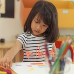 girl-drawing-color-pencils-in-kindergarten-classroom-preschool-a