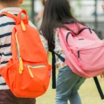 three-pupils-of-primary-school-go-hand-in-hand-boy-and-girl-with-school-bags-behind-the-back-beginning-of-school-lessons-warm-day-of-fall-back-to-school-little-first-graders_1253-1134